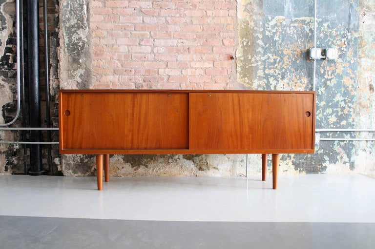 This credenza is a model 26, in oak, teak and brass, designed by Hans Wegner and produced in Denmark by Ry Mobler. The credenza features sliding doors that open to show a series of storage spaces, adjustable shelves, and drawers. The interior is
