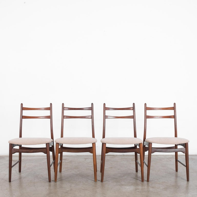 A set of four teak dining chairs, made in Denmark in the 1970s. Smooth, curving lines, tapering legs and a tilted seat angle update a classic dining chair design. An upholstered cushion in natural white creates a clean contrast with the rich tone of