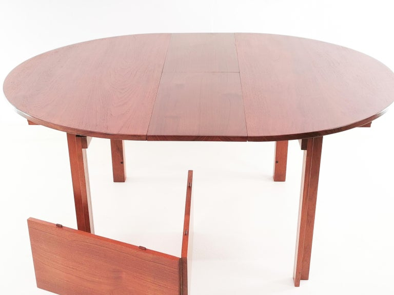 France and Son teak dining table  Offered for sale, a 1960s Danish extendable circular dining table made in Teak and designed by Inger Klingenberg. The dining table is a unique design that seats eight people comfortably due to the jack knife