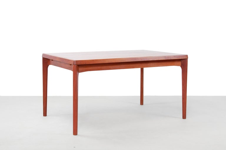 Danish modernist design extendable dining room table in teak. The extension leaves are nicely integrated into the design, stored under the table top, so that the table is both folded and unfolded nice to look at.  Special about this table is that
