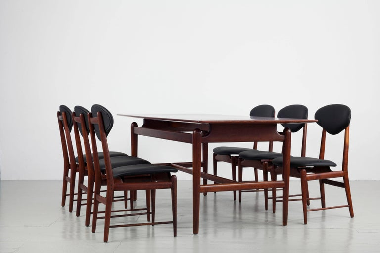 Teak dining table with a set of six dining chairs from Italy, 1950s. The teak wood is stained in a dark tone to immitate palisander wood. The chairs are made of teak with padding and upholstered with black leather. The unusual design element of