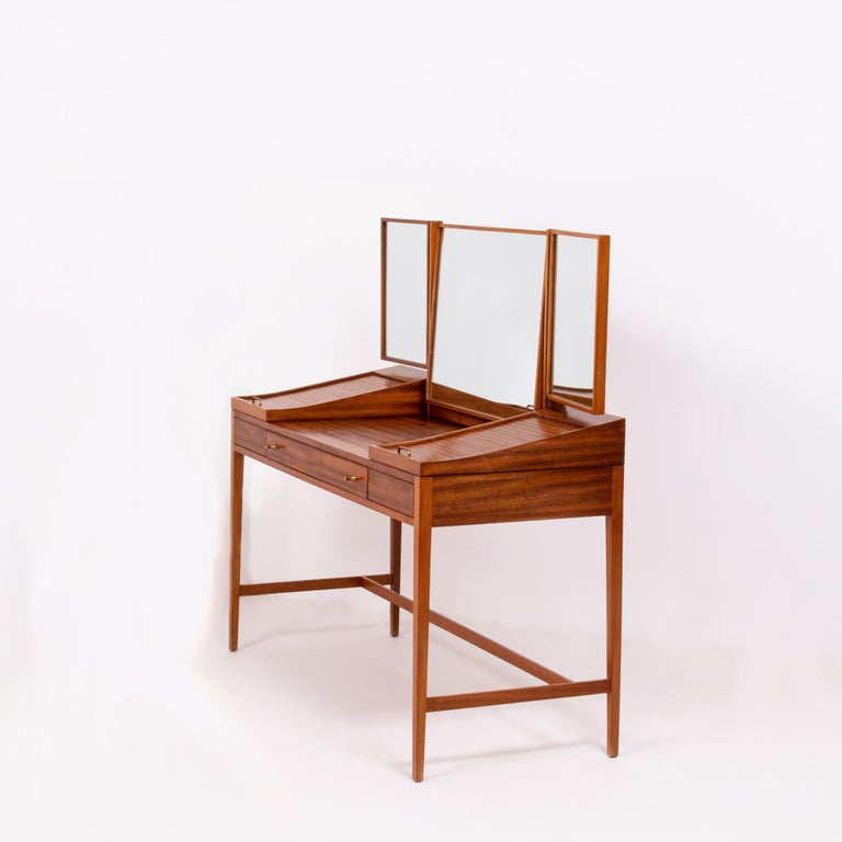 Designed by British furniture and interior designer Robert Heritage, this dressing table is beautifully constructed in teak wood.  The table features one large centre drawer, with two smaller drawers on either side and two additional compartments