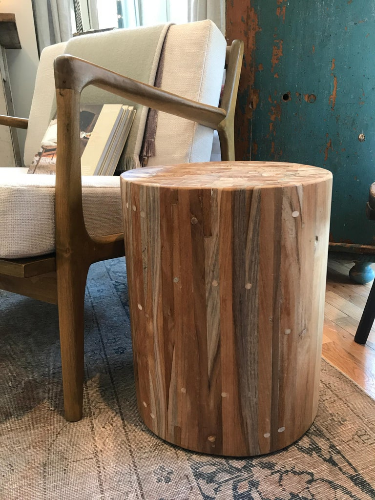 A subtle natural teak drum side table which can be versatility used as an ottoman, seat or stand for potted plants. Solid and very stabile.