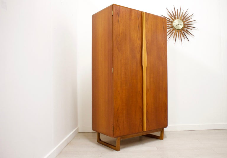 - Mid century modern wardrobe - Manufactured by Stonehill - Made from Teak & Teak Veneer - Featuring a hanging rail, interior cupboard with mirror and shelves.