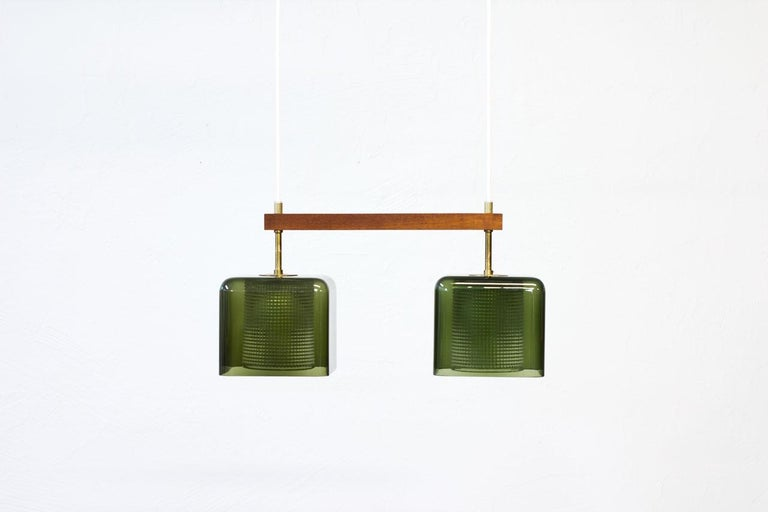 Pendant lamp designed by Carl Fagerlund for Swedish glass company Orrefors during the 1960s. Square shaped cups in green tinted glass with internal clear pressed glass diffuser, framed by a teak stretcher. Brass fittings with original brass ceiling