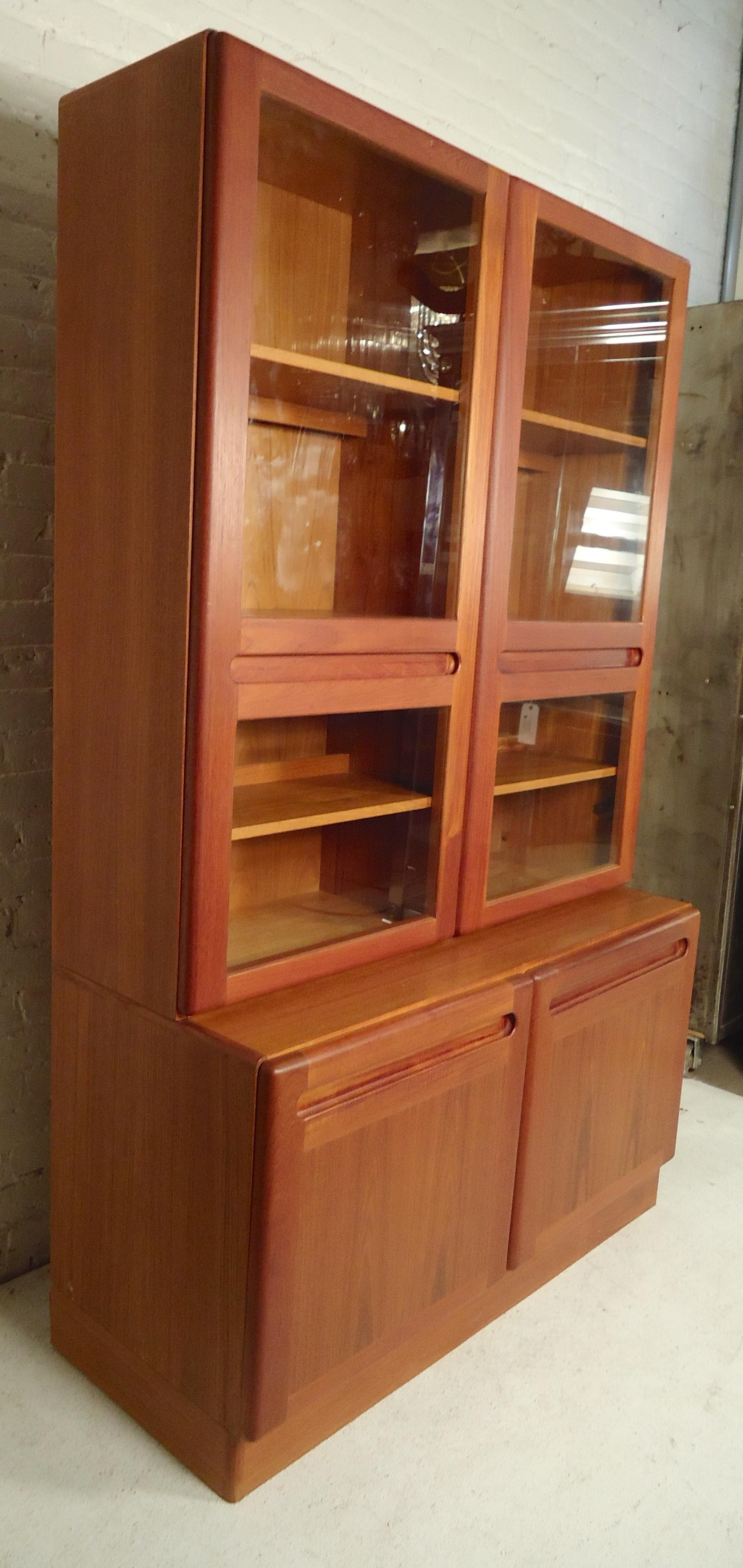 Stacked Bookcase With Cabinet Base. Glass Doors With Sculpted Handles And  Recessed Lighting Inside.