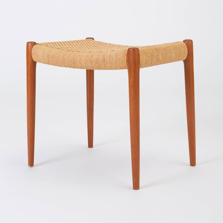 The model 80A ottoman, designed in 1963 by Niels Møller. A simple ottoman or footrest with Danish cord upholstery and slightly tapered legs, manufactured for Møller's family company, JL Møllers Møbelfabrik of Denmark. The cord seat, made of twisted