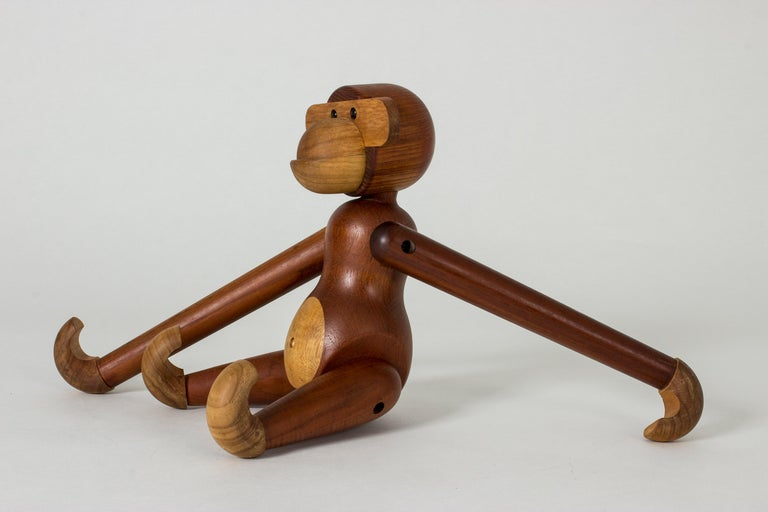 Large iconic teak monkey figurine by Kay Bojesen. Endearing, animated design. The limbs are fully movable and the monkey can hang by its hands or feet from a shelf or back of a chair.