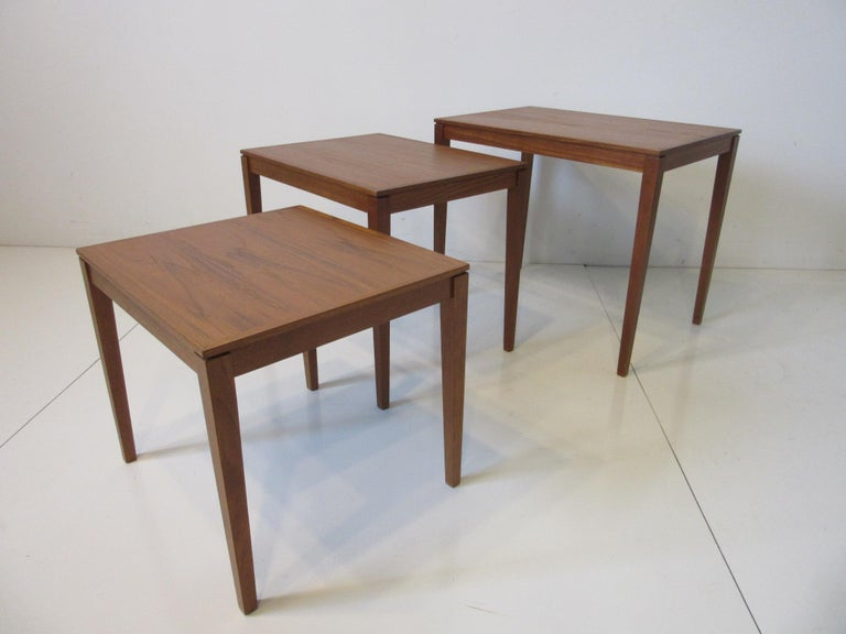 A set of three teak wood nesting side tables with wonderful graining and nice tapered side edges to the top retaining the manufactures branded marks to the bottoms by Bent Silberg Mobler made in Denmark.