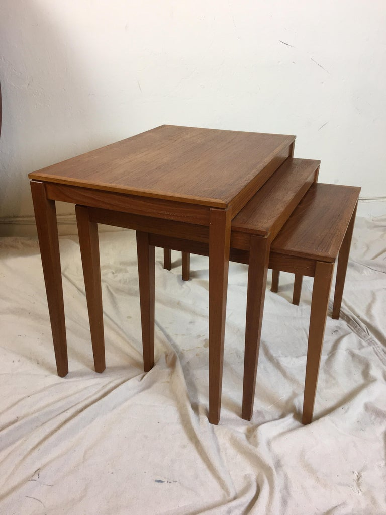 Set of 3 Bent Silberg's Mobler teak nesting tables. Nice grain and color. All three tables are the same depth 15.75 so they close up as basically one table. Very useful set! Largest table is 23.5 wide, middle table is 20.5 wide and small table is