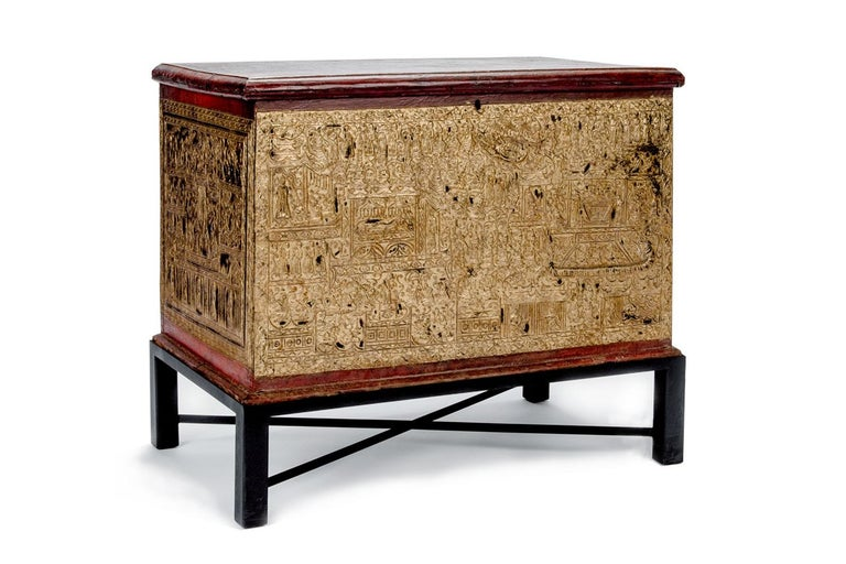 19th century teak Burmese manuscript chest. Made from teak and lacquered red with gold leaf accentuating depictions of the life of Buddha. Lid lifts open and sits on steel stand.  Measures: 38.5