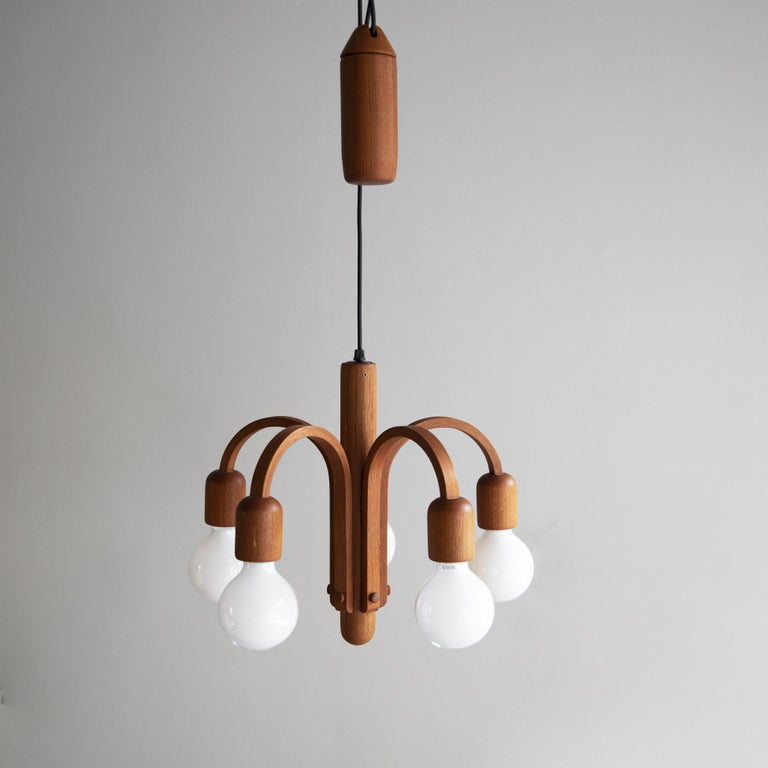A five-arm rise 'n' fall chandelier in teak, most probably made in Germany, circa 1960.  The centre of the light, from which the five arms extend, is a solid piece of teak carved into a torpedo shape. Echoing this are the bulb holders and the