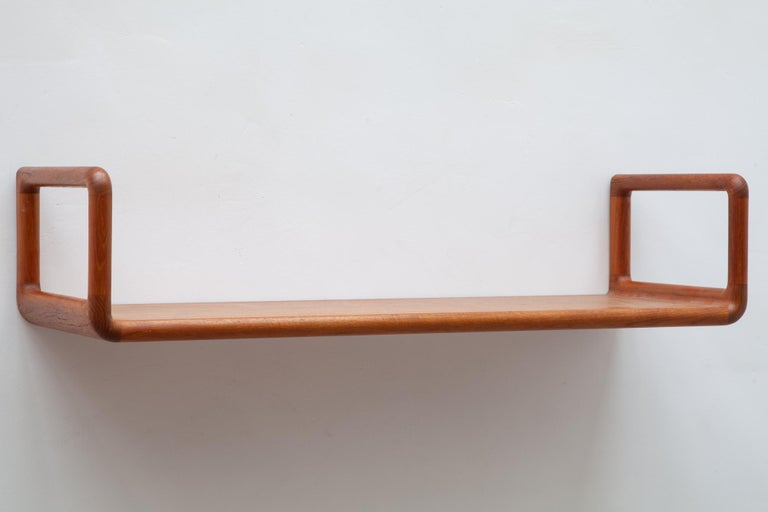 Danish teak wall shelves in classic midcentury design by Kai Kristiansen. Hanging style with soft rounded edges.