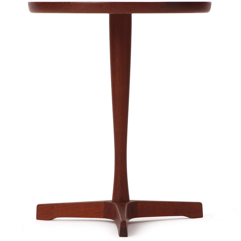 Circular teak occasional tables with black laminate inset top and tapered stem over a three-point base. Designed by Hans C. Andersen and produced in Denmark in the 1960s.