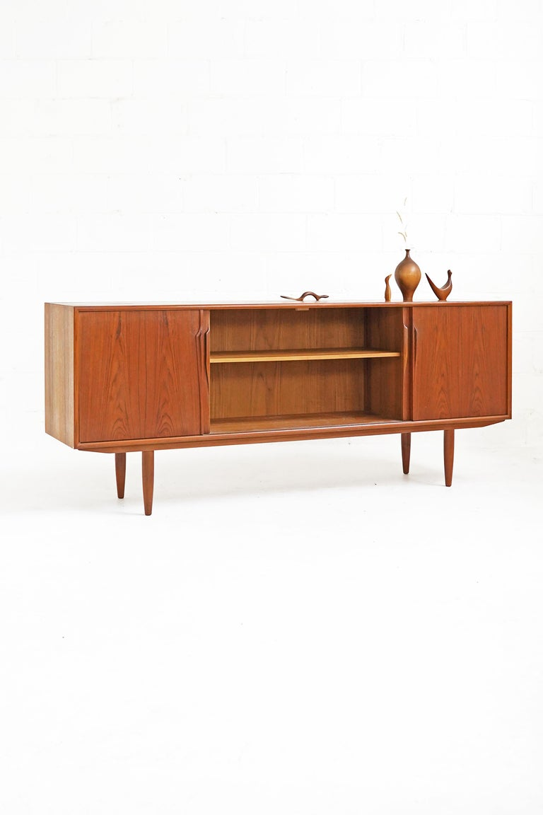 Stunning teak sideboard designed by Gunni Omann with beautiful bookmatched door fronts. In overall great vintage condition, has three inner drawers and two shelves.