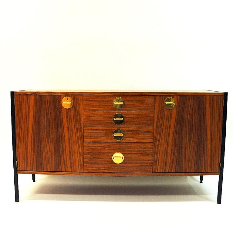 Vintage teak sideboard from the Triva modul series by Erik Herløw for Nordiska Kompaniet 1960s, Sweden. The sideboard has lovely brass details and the design is clean and Classic with a black steel frame around.