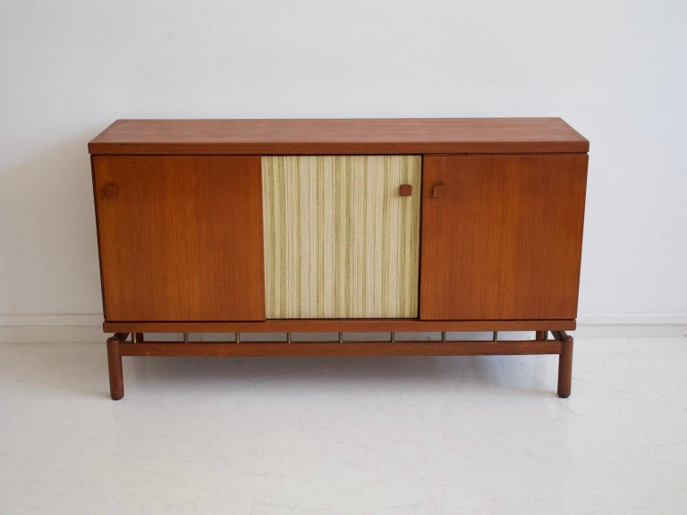Sideboard made of teak wood with brass details. Sliding doors, one of them decorated with fabric. Produced by La Permanente Mobili Cantù and designed by Ilmari Tapiovaara.  Literature: Selettiva Cantù Catalog.