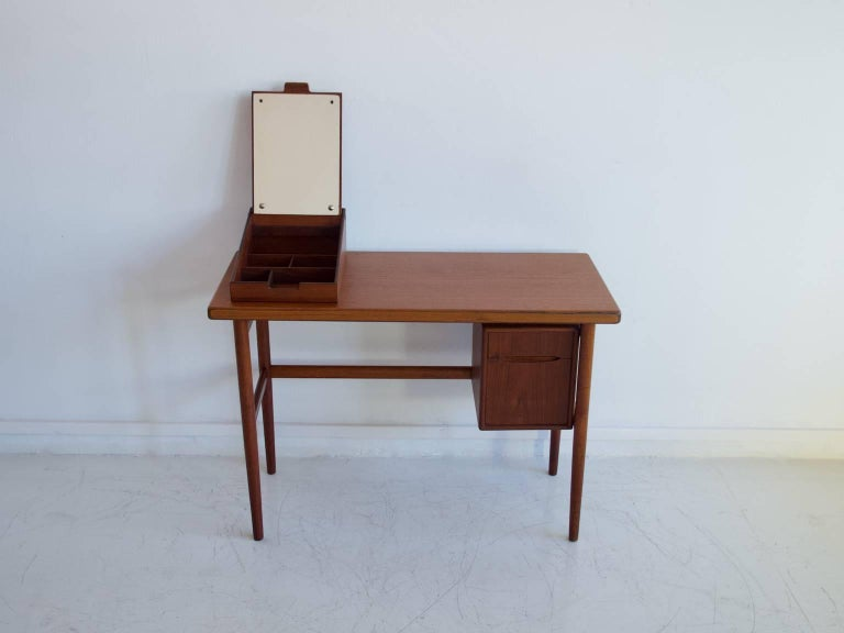 Danish dressing table from circa 1950-1960. Design attributed to Kurt Ostervig. Veneered with teak. The vanity features a compartment with a mirror on top of the table and drawers underneath. Restored, great condition. Measurements: The total height