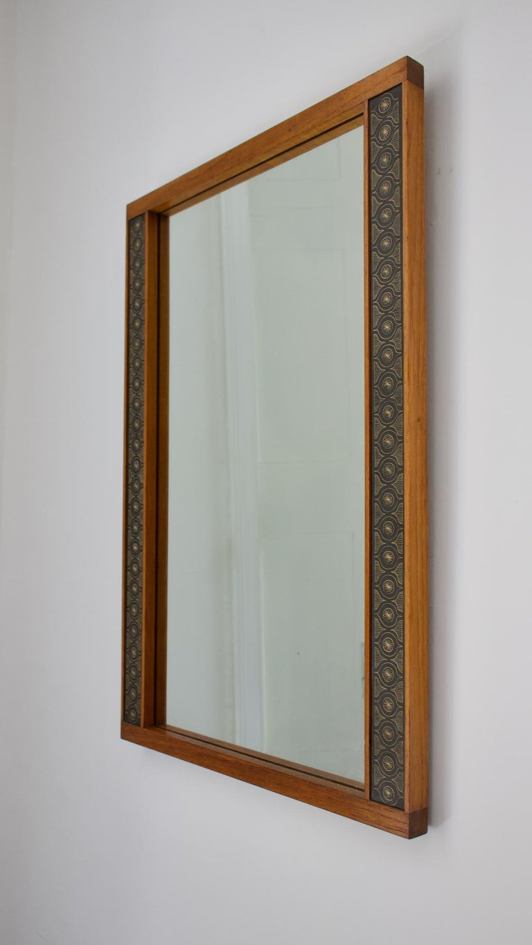 A teak wall mirror by Hans-Agne Jakobsson. Made in Åhus, Sweden, 1950s. Labelled to the reverse.  A very simple rectangular mirror with teak frame from the early years of Jakobsson's own work. The elegant frame is nicely made, and decorated to