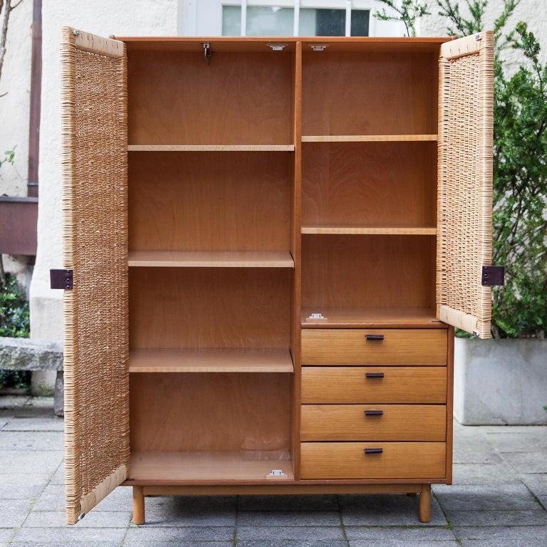 Sebastian Muggenthaler wardrobe with four drawers from 1960s. Wooden construction, teak veneer, teakwood, meshwork, leather.