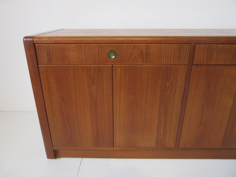 A medium dark toned teak server / chest / credenza with inset finger joint construction, four doors that have push touch latches and adjustable shelves. The two upper drawers have heavy brass pulls manufactured by D - Scan Singapore from the Captain