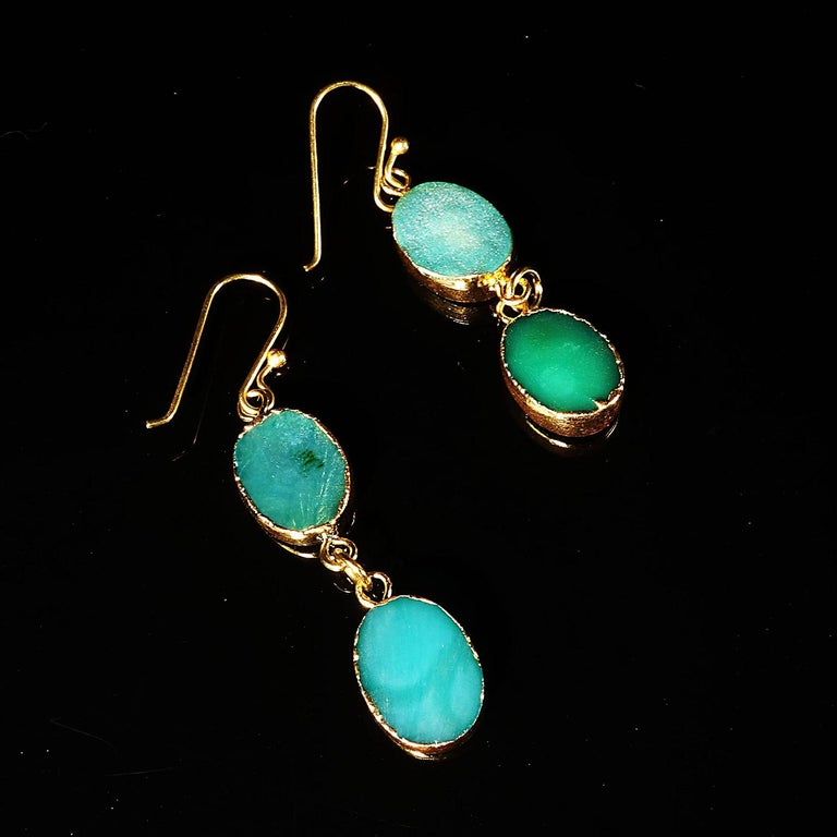 Delightful double dangle teal color Druzy earrings. These fun summer earrings each consist of two oval teal colored Druzy with goldy tone bezels. They hang from gold plated long hooks.  The entire ensemble is fun and funky.  They swing and dance
