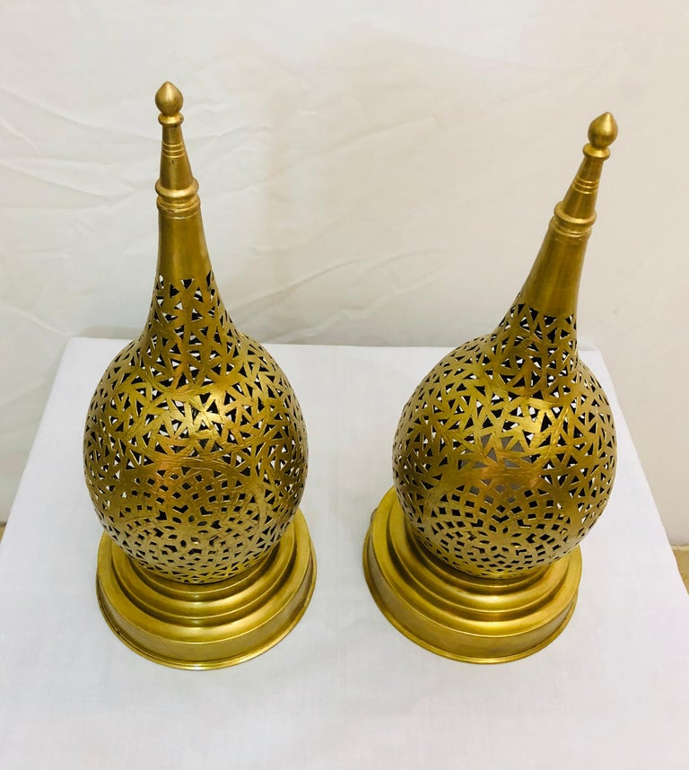 The intricate filigree design work of this handcrafted brass tear-shaped lamp will elevate the ambiance of any room. Featuring a wonderfully unique design aesthetic, these pair of table lamps emit a soft, filtered light.  Dimensions: 6.25