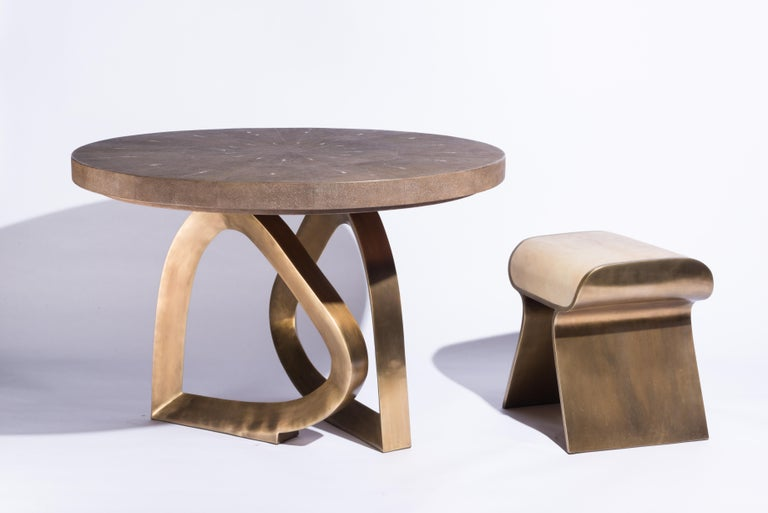 The teardrop breakfast table is a stunning piece, a statement in any space. The mink shagreen inlaid top creates warmth in any space with the brown tonalities in it, followed by the bronze-patina brass sculptural base. This piece is designed by Kifu