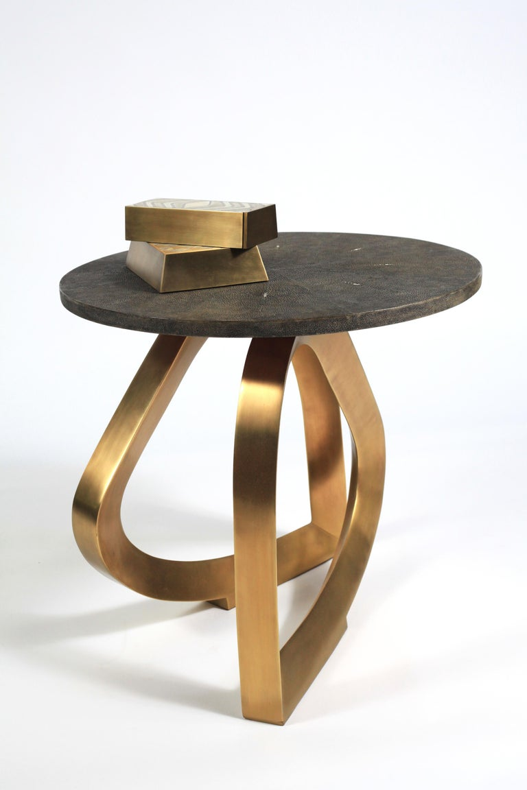 The Teardrop side table in black shagreen and bronze-patina is an elegant design with a circular top that sits on a sculptural base. The sculptural base is inlaid in bronze-patina brass and the top is in black shagreen. This piece is also available
