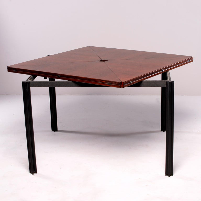 Rosewood table with black metal legs and tagged by Italian furniture maker Tecno, circa 1960s. Square top game table has unique hinged fold up leaves which are accessed by swiveling the tabletop which depresses the nickel button at center, allowing