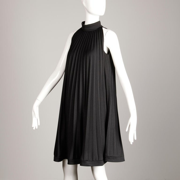 So mod! Vintage 1960s pleated A-line trapeze dress by Ted Lapidus. Fully lined with rear zip and hook closure. 100% medium weight polyester. The marked size is 38/12, but the dress fits more like a modern small-medium. The bust measures 37.5