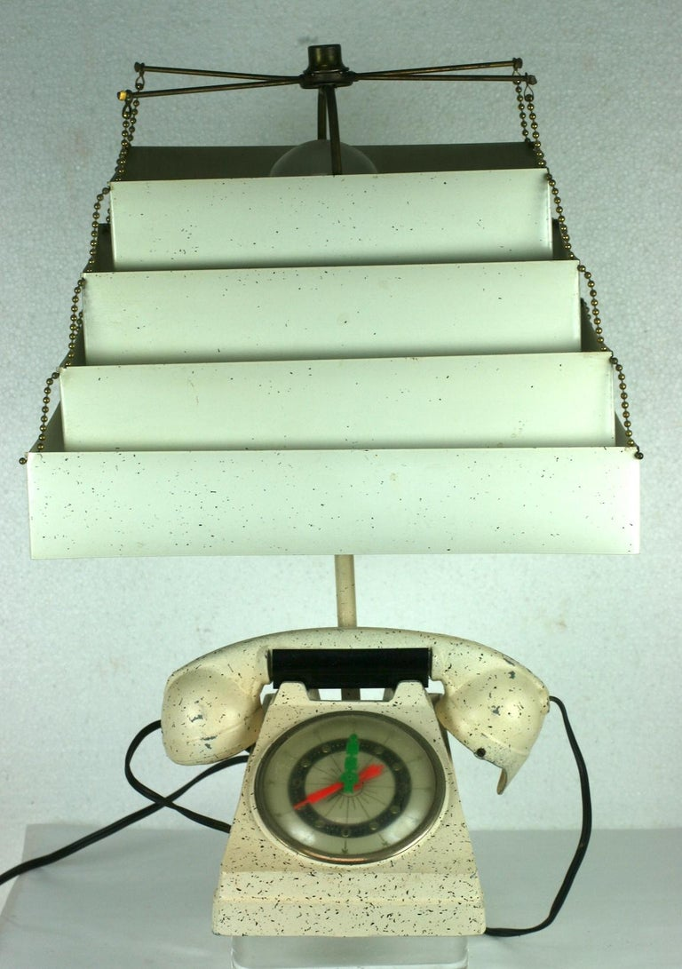 Incredibly kitsch and collectible telephone clock table lamp from the 1950s USA. It multitasks as a lamp, a cigarette lighter and a clock. The functioning clock has fluorescent hands in orange and acid green. The handset lifts to show a heat source