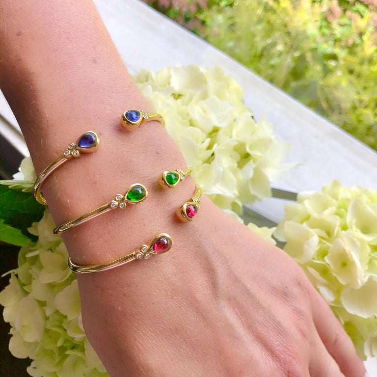 For the lover of all things green, this 18k yellow gold stackable cuff bangle bracelet is easy, fun and wearable. Designed with two bezel-set cabochon pear-shaped chrome diopside stones, weighing together 2.00cts., the clear and bright green