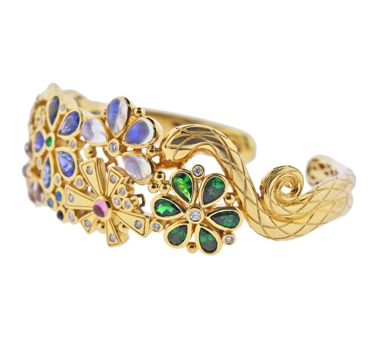 18k gold cuff bracelet by Temple St. Clair, decorated with moonstone, emeralds, sapphires and approx. 0.48ctw in diamonds. Bracelet will fit approx. 7.25