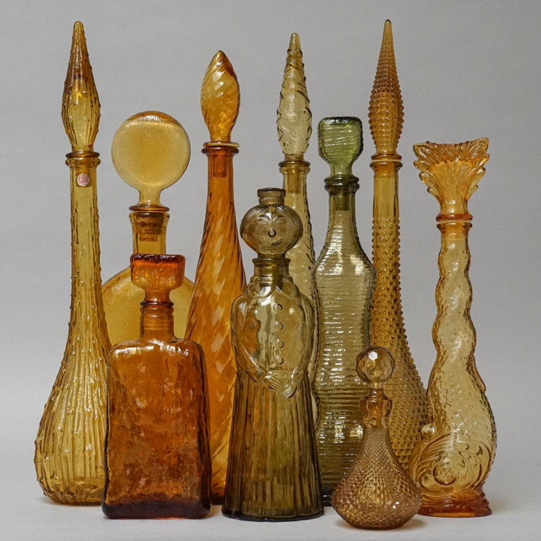 Extraordinary set of ten large vintage glass 'genie bottle' decanters with different shapes in golden amber yellow. Look at these different shades of 'Golden' colors and all these pretty shapes. They used to be filled with different kinds of