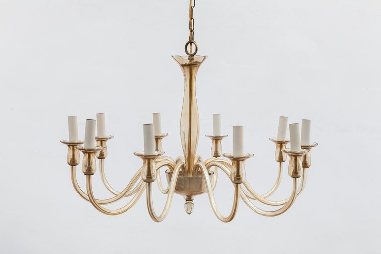 Hollywood regency style chandelier in warm amber colored glass with brass tone hardware. 10 arms with candelabrum sized sockets. Dimensions: 83 W x 51 H cm, chain length 150 cm.