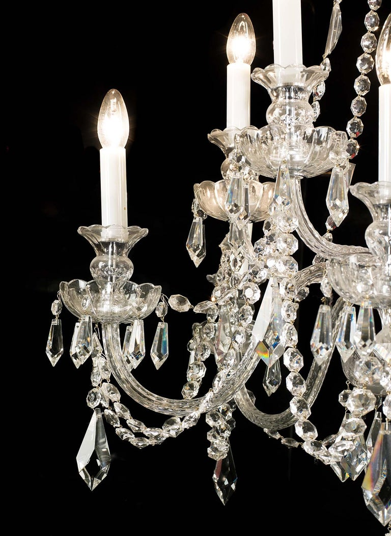 A ten branch cut-glass chandelier, with shaped baluster stem issuing two graduated tiers of swan neck branches, all with lustre drip pans interlinked with cut glass chains. Late 20th century.