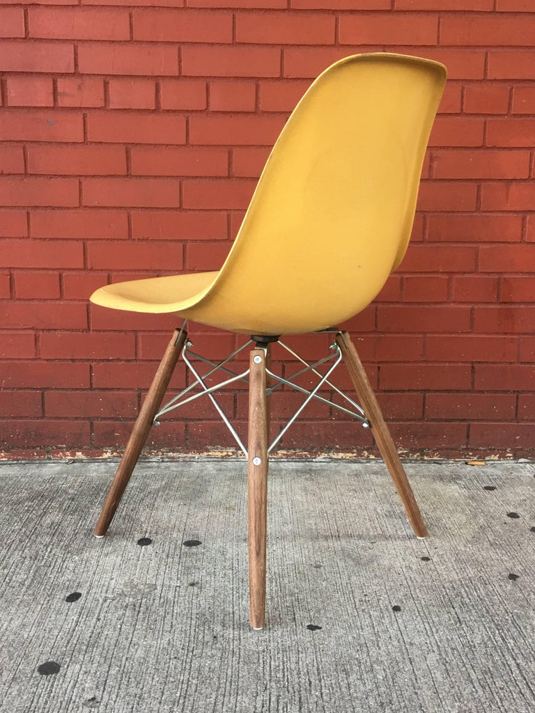 Ten Herman Miller Eames dining chairs in Ochre light. New walnut stained bases with black metal (base pictured in individual photo).