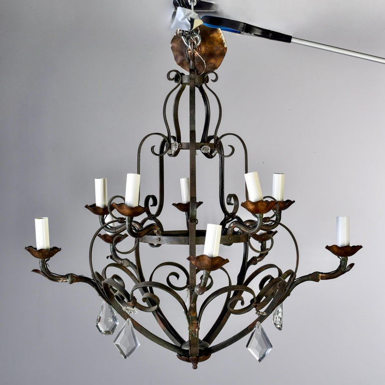This circa 1930s French hand forged metal ten-light chandelier has a bowl shaped base with two tiers of 5 candle style lights, curved iron arms, contrasting copper tone candle cups, and large, faceted crystal pendant drops. Ten candelabra sized
