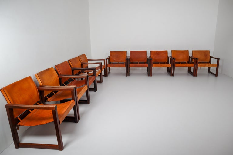 Set of ten safari lounge chairs in absolutely gorgeous patinated cognac saddle leather and solid pinewood, circa 1970s. The thick saddle leather is beautifully patinated during use and age and shows interesting stitching. There is a color difference