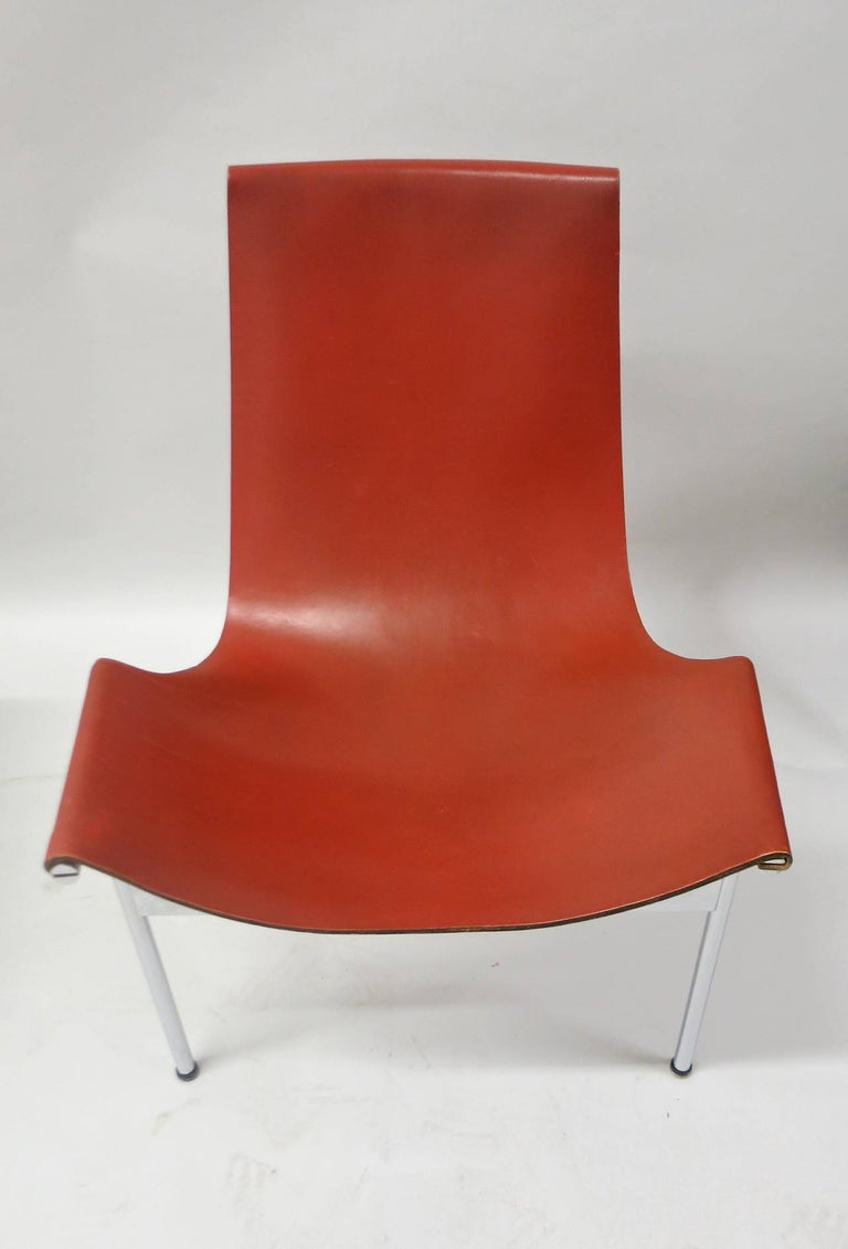 Rare set of ten T-chairs with special ordered leather backing that is in a matching tone as the front red-brown saddle leather. All have minimal wear and have had very careful use. The chromed bases are in very good to excellent-vintage condition.