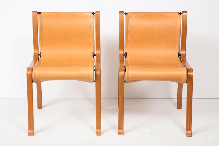 Ten saddle stitched leather and bentwood dining chairs by Valdes Two arm (B model) and eight side (A model) cognac patina saddle stitched leather with bentwood frame and steel tubing chairs. Handmade the old fashion way in Chile. The B model is in