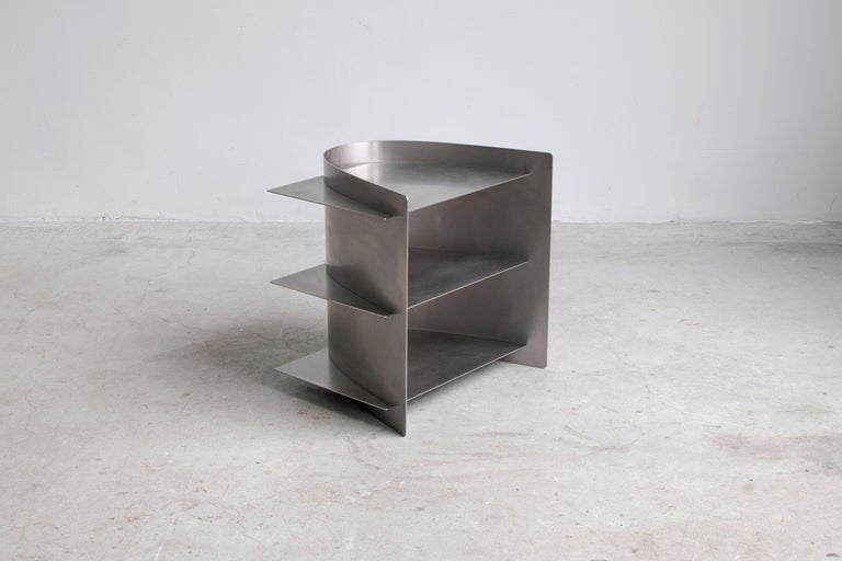 Tension side table, Paul Coenen Dimensions: 50 x 45 x 50 cm Materials: Sanded and waxed stainless steel  Custom colors and materials are possible on request.  Tension Collection The manufacturing industry is using standard sized material, and