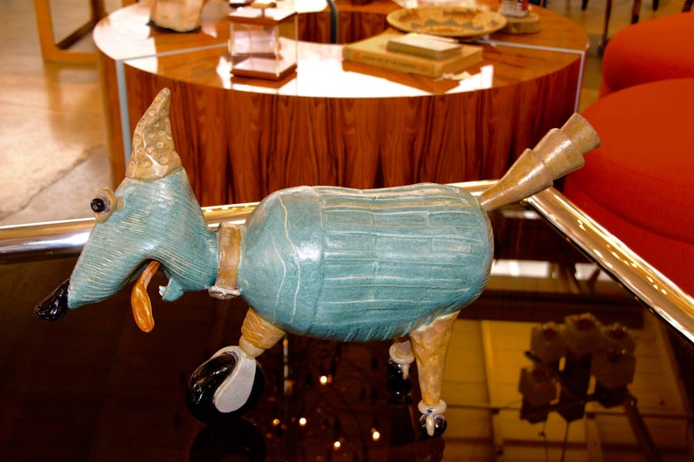 A whimsical terracotta Caricature of a dog, or a comic figure. The creatures has three-legs which end in wheels. The head is adjustable. Not signed that we can find. Some glaze loss and repairs to tongue and ears, that are apparent. There may be