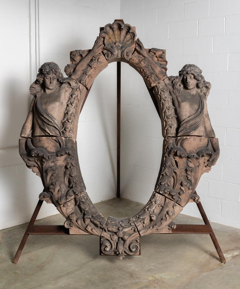 Terracotta Figural Architectural Window Surround, America 19th century.   Incredible, large-scale architectural element includes decorative detailing and two figures flanking each side. Can be installed on the accompanying iron stand or more