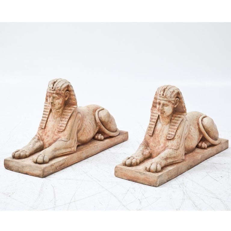 Pair of red patinated terracotta sphinxes on rectangular pedestals.