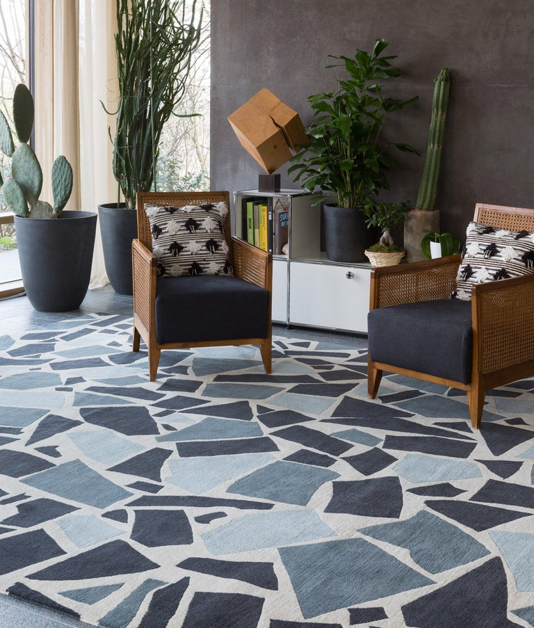 Inspired by 1950s terrazzo floors, this rug design has been given a modern update with a versatile palette of blues and greys on a cream background. The chunkier knot used to create this rug gives it a wonderful texture underfoot and a lower