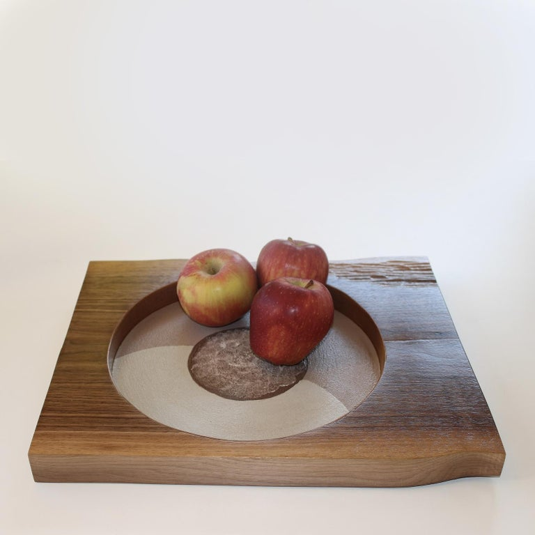Part of an exclusive collection of only 20 pieces, this wooden tray was handcrafted of walnut and entirely decorated by hand. Its rectangular Silhouette is adorned at the center with a deep round inlay with a central accent in it. The piece is