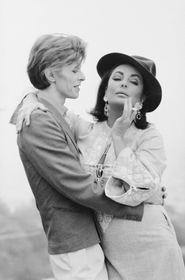 Terry O'Neill Black and White Photograph - David Bowie and Elizabeth Taylor, Beverly Hills, 1975