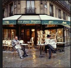 Elton John and Bernie Taupin sitting outside Aux Deux Magots
